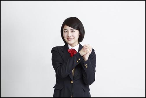 手を握りしめ笑顔の女子高生の画像