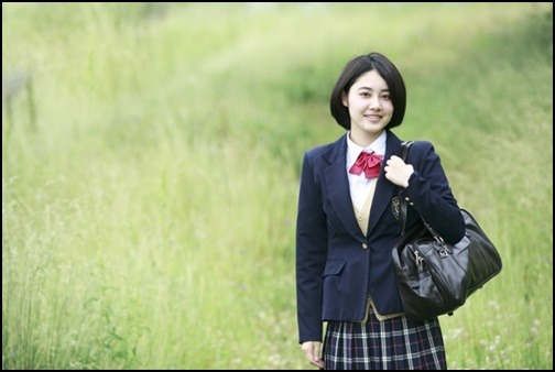 草原で笑顔の女子高生の画像