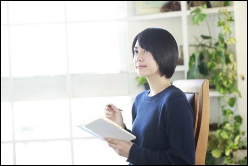予定を書き込む女性の画像