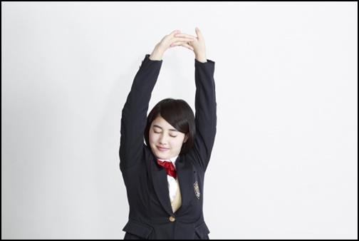 背伸びをしている女子高生の画像