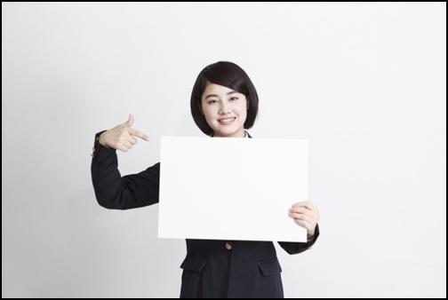 ホワイトボードを持って見せる女子高生の画像