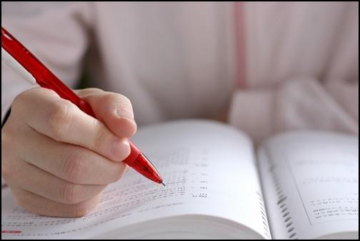 赤ペンを持って勉強している画像