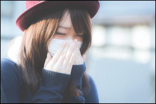 マスクをくしゃみしている女性の画像