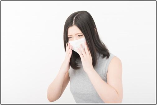 くしゃみをする女性の画像