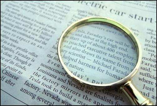 英語の新聞と虫眼鏡の画像