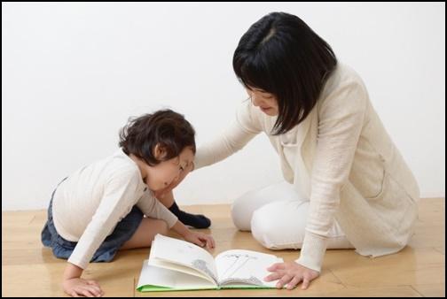 母親が幼児に絵本を読み聞かせしている画像