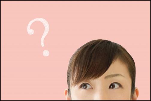 ?マークの疑問を掲げる女性の画像