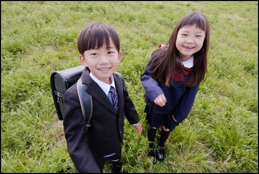 小学生1年生の男女が草原で笑顔でほほ笑む画像