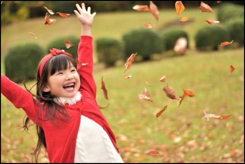 落ち葉で遊ぶ女の子の画像