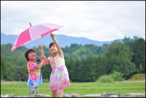 傘をさす女の子と男の子の画像