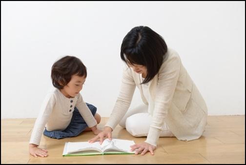母と子供が絵本を読んでいる画像