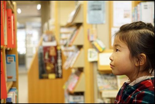 図書館で本を見る女の子の画像