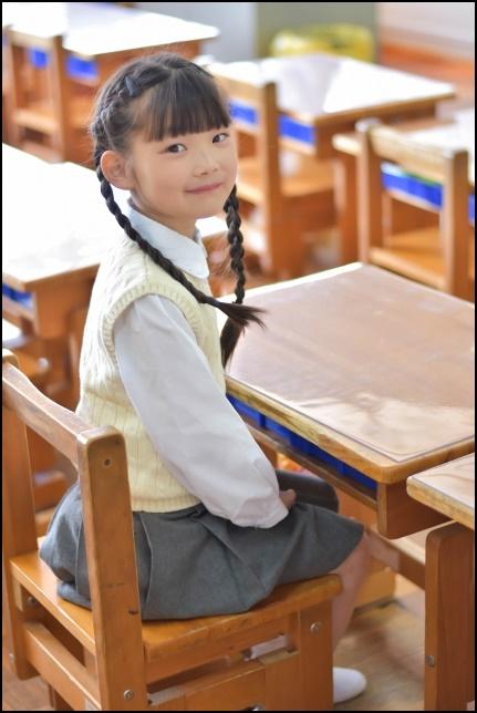 教室に席に着席する小学生の女の子の画像