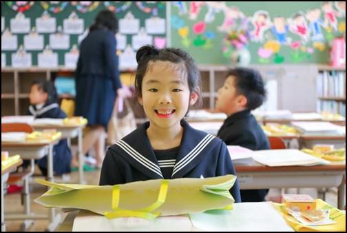 学校の机に制服で座って笑顔の小学生女の子の画像