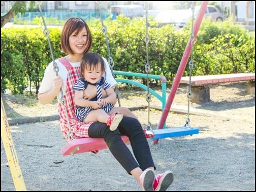 お母さんが赤ちゃんを抱えてブランコに乗る画像