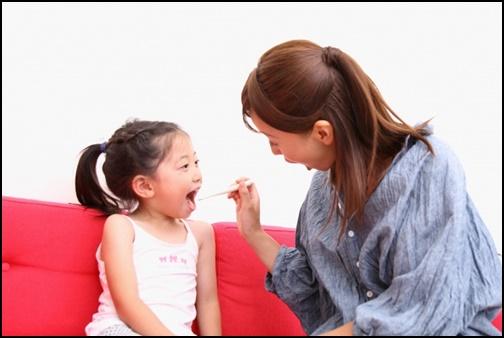 女の子に歯磨きを指導している母親の画像