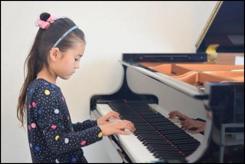 グランドピアノを弾く女の子の画像