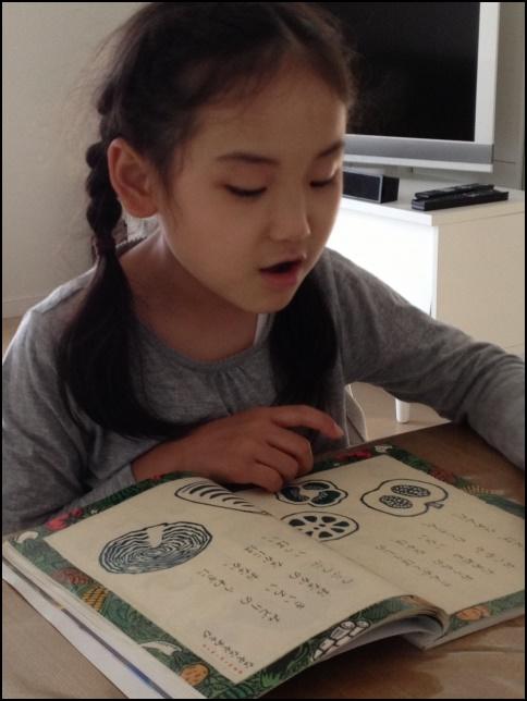 国語の教科書を音読する小学生の女の子の画像