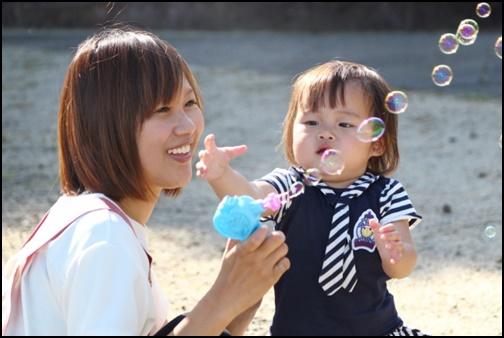 シャボン玉で遊ぶ女性と2歳児の画像