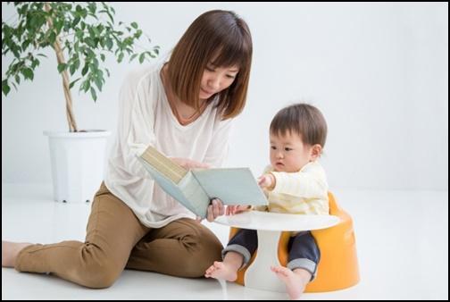 幼児に絵本を読む母親の画像