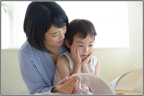 母親と子供が絵本を読む画像