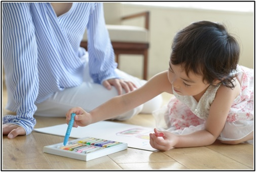 母親が子供のお絵描きを見守る画像