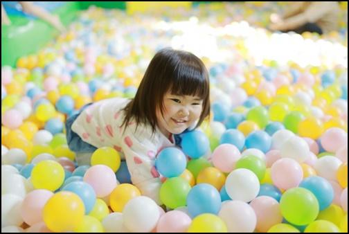 2歳児の女の子がボールプールで遊ぶ画像