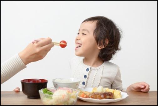 母親にご飯を食べさせてもらって笑顔の子供の画像