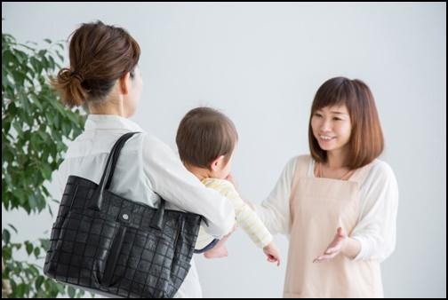 お母さんが保育士さんの子供を預ける画像