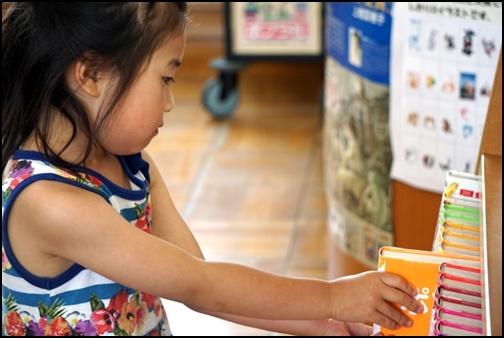 女の子が図書館で本を選ぶ画像