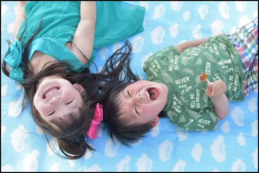 男の子と女の子が寝転びながらほほ笑む画像