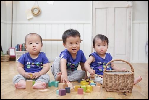 1歳児が3人座って遊んでいる画像