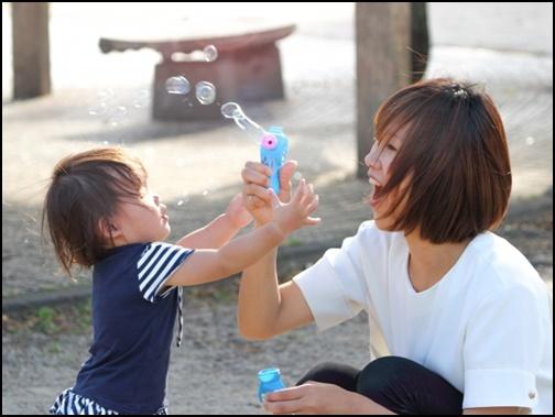 幼児と母親が公園でシャボン玉で遊ぶ画像