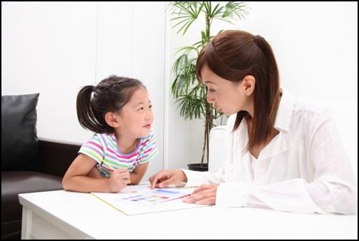 母親と娘が絵本でお勉強している画像