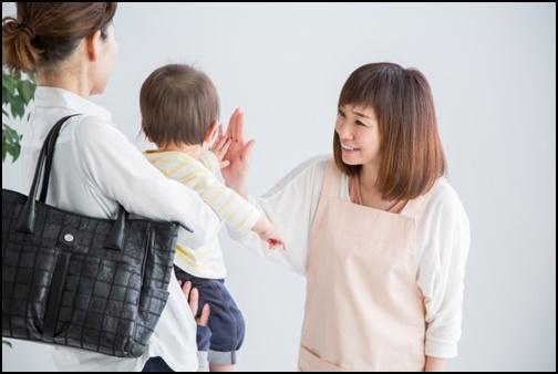 子供を保育士に預ける母親の画像