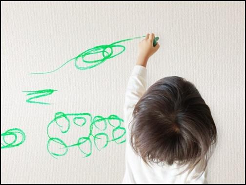 壁にお絵描きする子供の画像