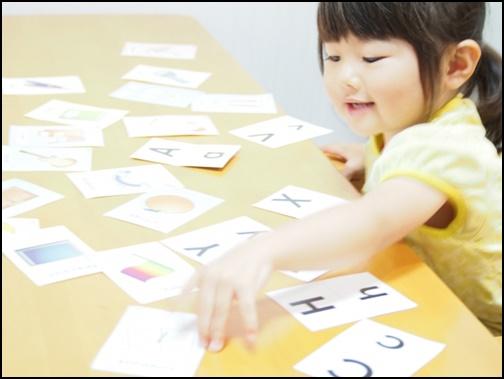 女の子が英語のカードを選ぶ画像