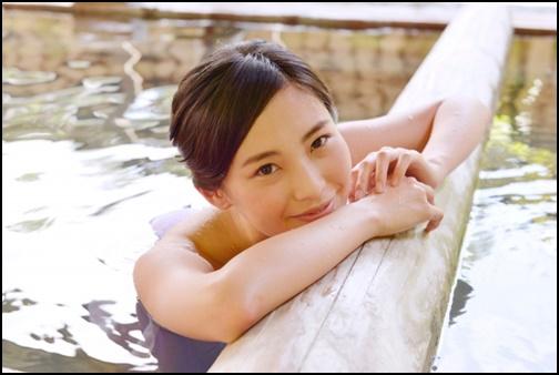 温泉に入って笑顔の女性の画像