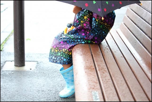 長靴を履いてカッパを着てバス停で待っている女の子の画像