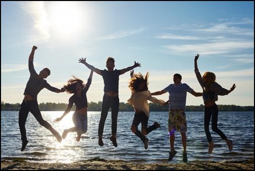 浜辺で仲間とジャンプする画像