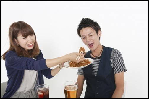 女性が男性に焼きそばを食べさせる画像