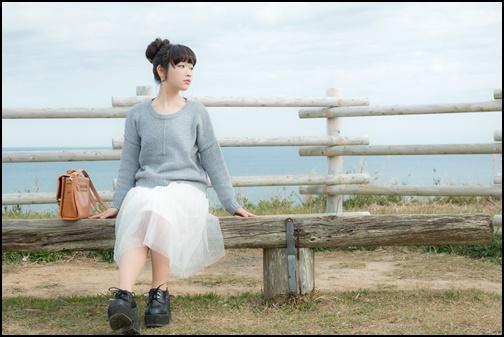 海辺のベンチでぼーっとする女子大生の画像