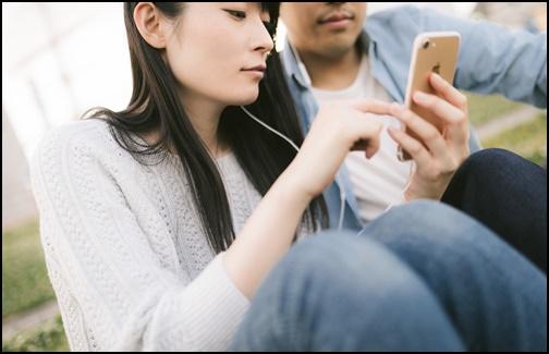 彼氏とスマホを見る女性の画像