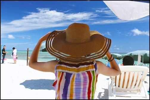 ビーチで麦わら帽子をかぶツ女性の画像