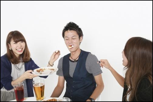 飲み会で女性が男性にご飯を食べさせる画像
