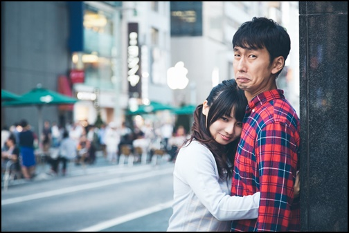 女性に抱き着かれて困っている男性の画像