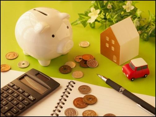 貯金箱と小銭と計算の画像