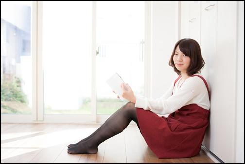 小説を読んでいる女性がこちらを見ている画像