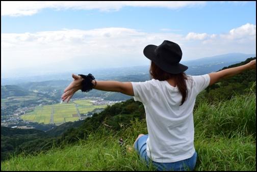 Tシャツを着て腕を広げて山頂を楽しむ女性の画像