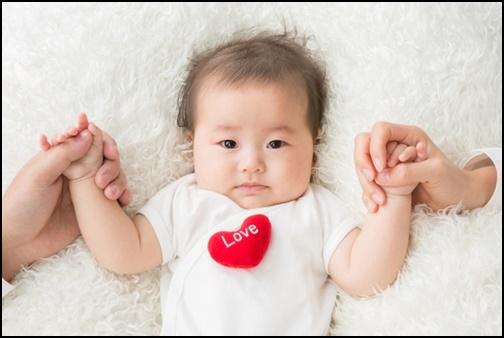 赤ちゃんが母親と父親に手を繋がれて見ている画像